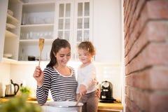 Мать при ее дочь в кухне варя совместно Стоковое Изображение