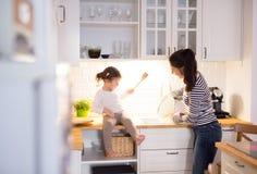 Мать при ее дочь в кухне варя совместно Стоковые Фото