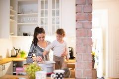 Мать при ее дочь в кухне варя совместно Стоковое фото RF
