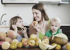 Мать при дети есть дыню стоковое изображение rf