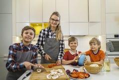 Мать при дети режа ингридиенты для пиццы Стоковое Фото