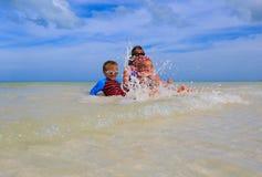 Мать при 2 дет брызгая воду на море Стоковое Фото