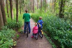 Мать при 2 дет ехать велосипеды в лесе Стоковая Фотография