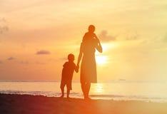 Мать при 2 дет идя на пляж захода солнца Стоковые Фотографии RF