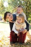 Мать при 2 дет обнимая в парке осени Стоковое Изображение RF