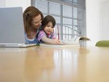 Мать при компьтер-книжка помогая дочери в книжка-раскраске на таблице Стоковое фото RF