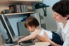 Мать при маленькая дочь работая на компьютере Стоковые Фото