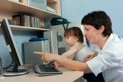 Мать при маленькая дочь работая на компьютере Стоковая Фотография