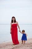 Мать при малыш гуляя на пляж песка Стоковые Изображения