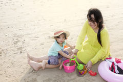 Мать при маленькая девочка играя на пляже Стоковая Фотография
