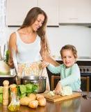 Мать при маленькая дочь варя дома Стоковое Изображение