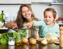 Мать при маленькая дочь варя дома Стоковые Фото