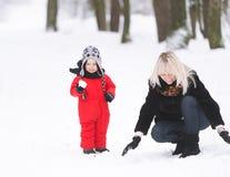 Мать при мальчик играя в снеге Стоковая Фотография RF