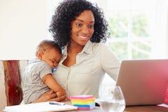 Мать при младенец работая в офисе дома стоковые фотографии rf