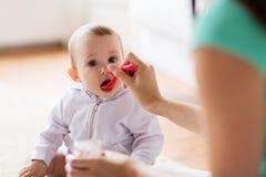 Мать при ложка подавая маленький младенец дома Стоковая Фотография RF