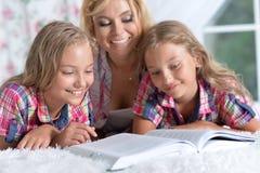 Мать при 2 прелестных близнеца делая домашнюю работу Стоковое Изображение