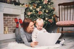 Мать при ребенок среди украшений рождества читая рассказ в a Стоковые Фото