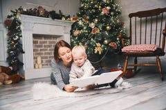 Мать при ребенок среди украшений рождества читая рассказ в a Стоковое Изображение