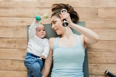 Мать при ребёнок лежа на поле и играя с гантелями Стоковые Изображения RF