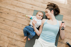 Мать при ребёнок лежа на поле и играя с гантелями Стоковое Изображение RF