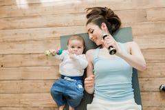 Мать при ребёнок лежа на поле и играя с гантелями Стоковые Фотографии RF