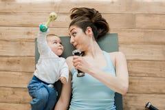 Мать при ребёнок лежа на поле и играя с гантелями Стоковое фото RF