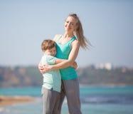 Мать при сын отдыхая на пляже Стоковые Изображения