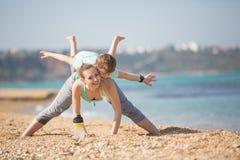 Мать при сын работая на пляже Стоковые Изображения