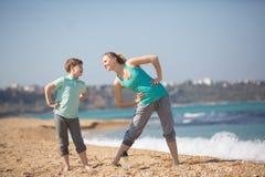 Мать при сын работая на пляже Стоковое Фото