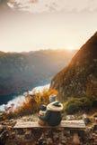 Мать при сын смотря заход солнца в горах Стоковые Изображения RF