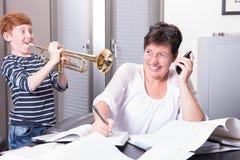 Мать работает в домашнем офисе, сыне нарушает путем играть t Стоковое фото RF