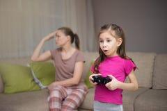 Мать расстраивая то ее doughter играя видеоигры стоковое фото