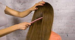 Мать расчесывая волосы дочери длинные после ванной комнаты Стоковая Фотография