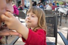 Мать ребенк подавая с слойкой сыра в внешнем кафе Стоковое Изображение RF