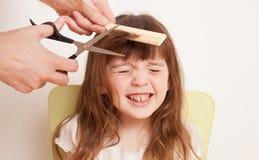 Мать режет волосы ` s дочери дома стоковые фото