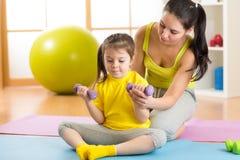 Мать семьи и дочь ребенка приниманнсяый за фитнес, йога, работают дома или зала спорта Стоковое фото RF