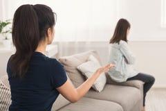 Мать смотря дочь которая сидя грустно на софе стоковое изображение rf