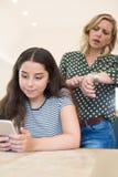 Мать споря с дочь-подростком над пользой мобильного телефона Стоковые Фото