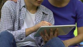 Мать сына уча для использования мобильного применения на современном планшете, ходить по магазинам онлайн видеоматериал