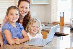 Мать с дет на их компьтер-книжка в кухне Стоковое Фото