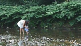 Мать с дочерью идет вдоль реки акции видеоматериалы