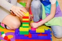 Мать с дочерью построила башню от кирпичей игрушки Стоковые Изображения