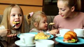 Мать с ее маленькой дочерью в кафе связывать пока ждущ заказ сток-видео