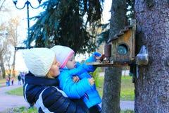 Мать с ее дочерью подает птицы в парке Стоковое Изображение RF