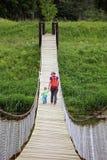 Мать с ее прогулкой сына малыша на висячем мосте adventurousness стоковая фотография rf