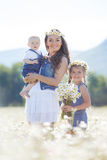 Мать с детьми в поле лета зацветая маргариток Стоковое Фото