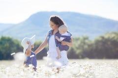 Мать с детьми в поле лета зацветая маргариток Стоковые Фотографии RF