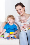 Мать с детьми на софе Стоковое фото RF