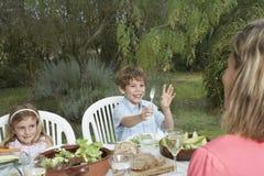 Мать с детьми на таблице в саде Стоковые Изображения RF