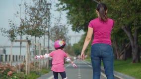 Мать с кататься на коньках ролика дочери в парке сток-видео